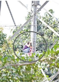 抱3岁大女儿跳高压电塔